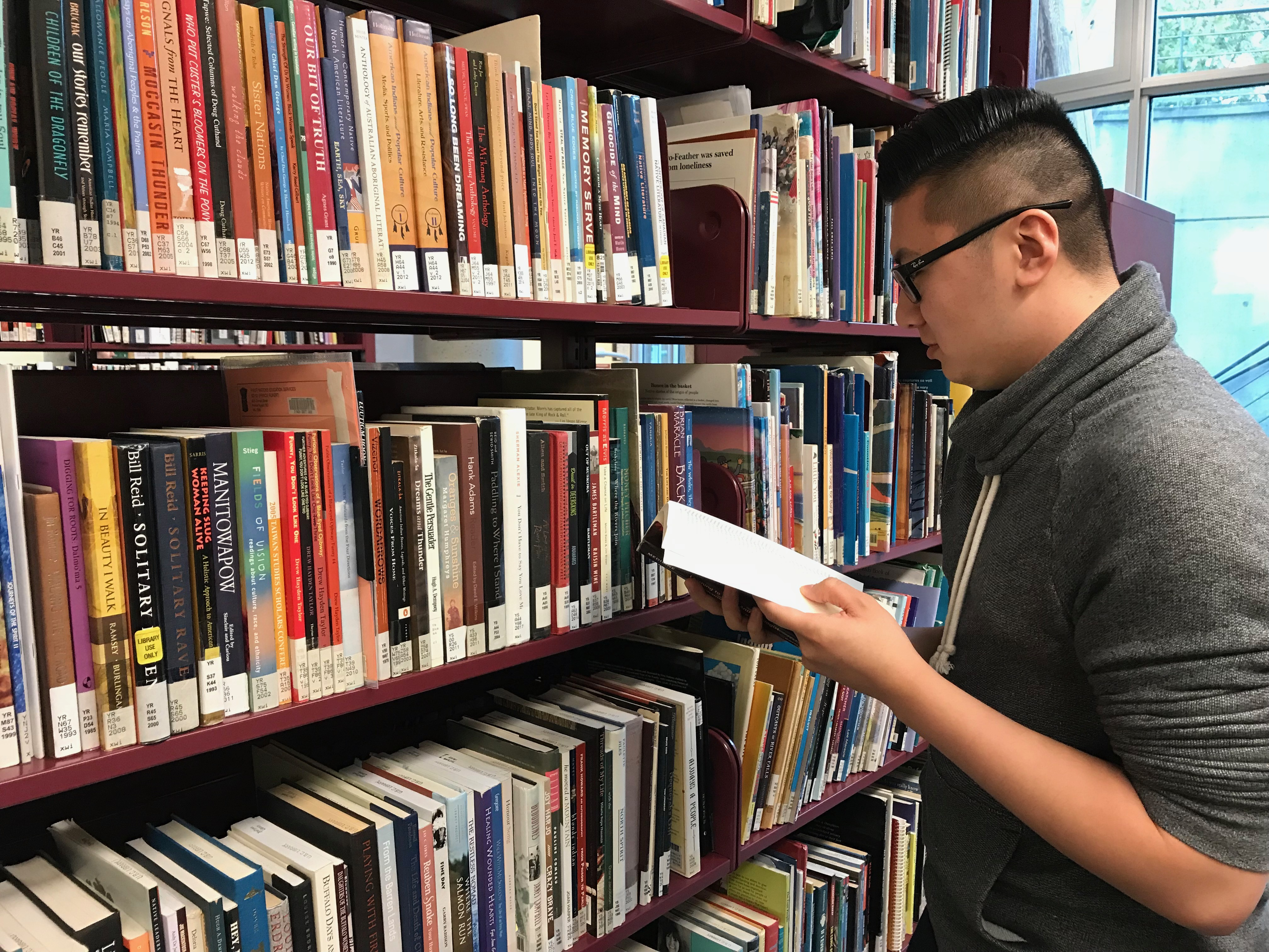 man with book in library