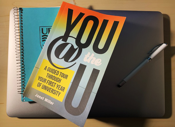 A photograph of the book You at the U with a teal blue notebook, both sitting on a silver laptop